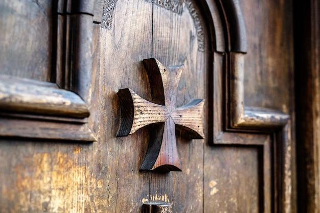 マルタ十字のクローズアップと古い木製のドア