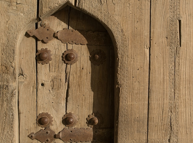 Old wooden door with metal rivets in bukhara, central asia.