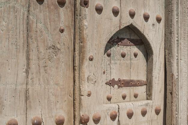 중앙 아시아 부하라에 금속 리벳이 있는 오래된 나무 문.