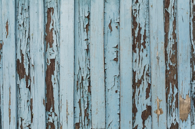 Old wooden door with peeling and cracked white and blue paint.