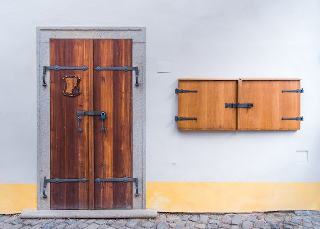 Old wooden double door on concrete white wall with small wooden window on the side