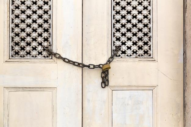 Старая деревянная выцветшая дверь заперта цепью