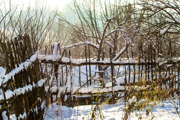 Старый деревянный забор в саду зимой в солнечную погоду. сельский зимний пейзаж