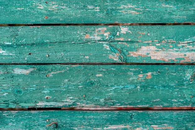 Old wooden fence light green paint peeling board texture background
