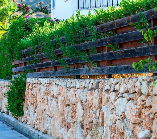 Старый деревянный забор с цветами и травой
