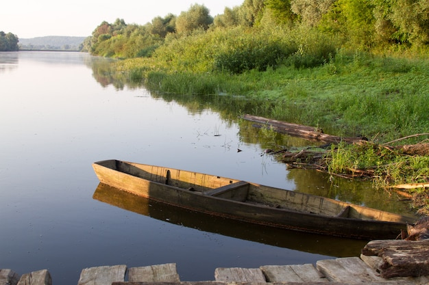 Old wooden fishing boat anchored by the green bank of the river