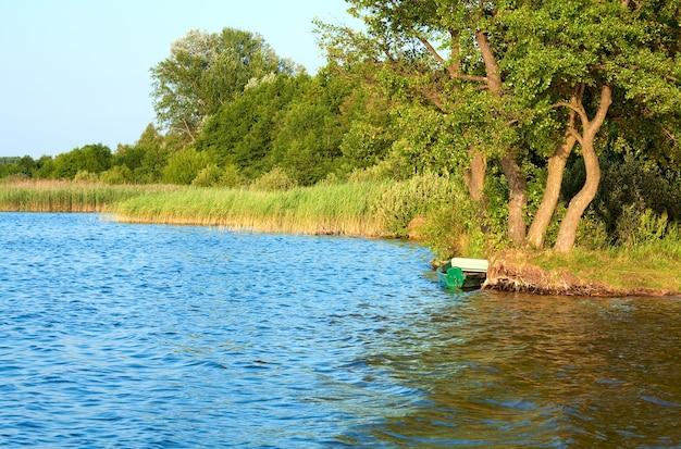 夏の湖岸近くの古い木製の漁船(svityaz、ウクライナ)