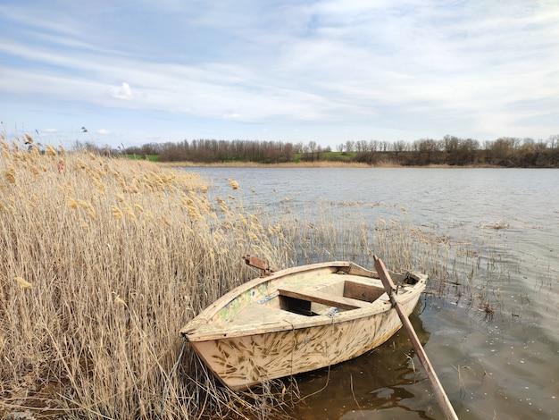 川や池の海岸にある古い木製の漁船