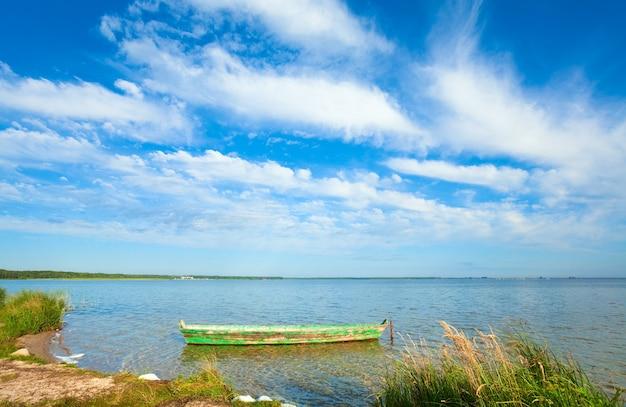 夏の湖岸にある古い木製の漁船(svityaz、ウクライナ)