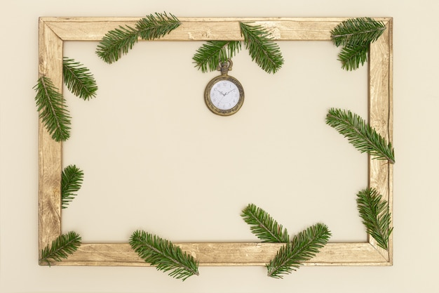 Old wooden frame with green fir tree branches and vintage pocket watch show 10 oclock