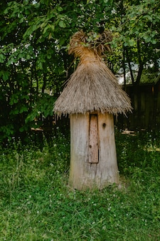 Old wooden hive with thatched roof