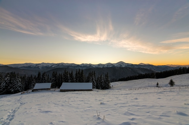 Old wooden house, hut and barn in deep snow on mountain valley, spruce forest, woody hills on clear blue sky at sunrise . mountain winter panorama landscape.