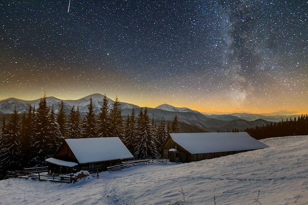 Old wooden house, hut and barn, pile of firewood in deep snow on mountain valley, spruce forest, woody hills on dark starry sky and milky way. mountain winter night landscape.