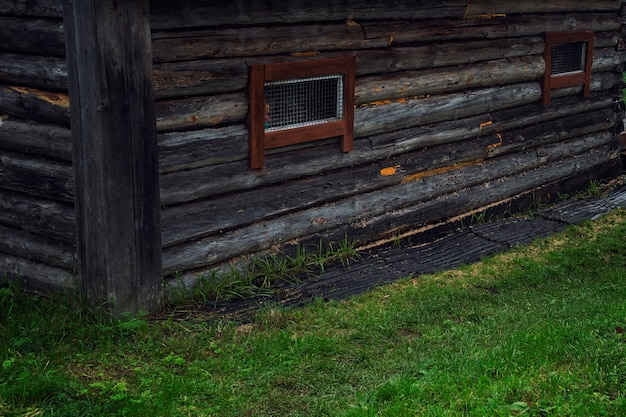 An old wooden house with metal bars on small windows. close-up. home prison.