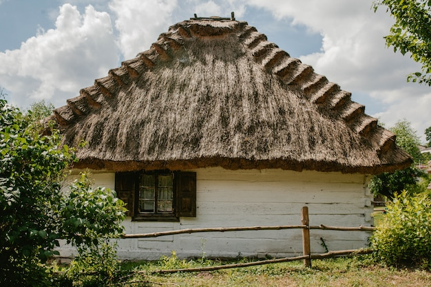 Old wooden house with a straw roof and garden