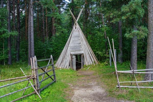 森の中の円錐形の棒で作られた古い木造の小屋。
