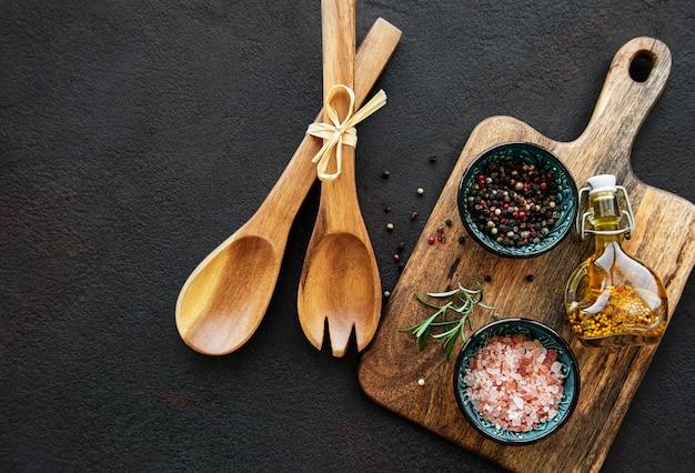 黒の背景に古い木製の台所用品とスパイス