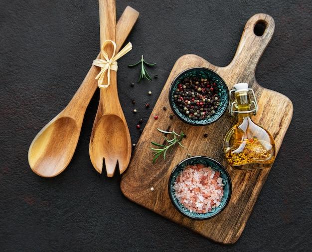 Старая деревянная кухонная утварь и специи на черной поверхности