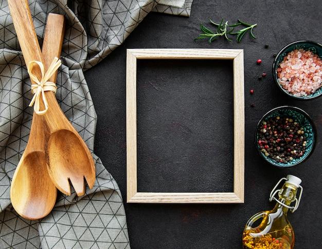 黒い表面の境界線としてフレームが付いている古い木製の台所用品とスパイス