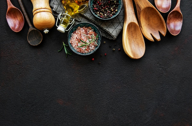 Old wooden kitchen utensils and spices as a border on a black background