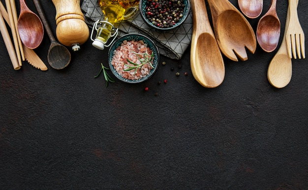 Old wooden kitchen utensils and spices as a border on a black surface