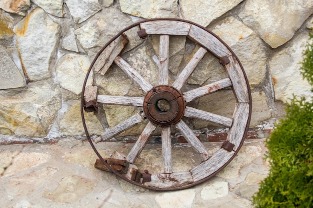 Old wooden and metall wheel on stone wall background