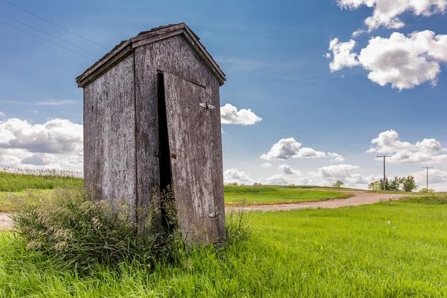 Старая деревянная уборная во дворе в сельской местности прерии в саскачеване, канада