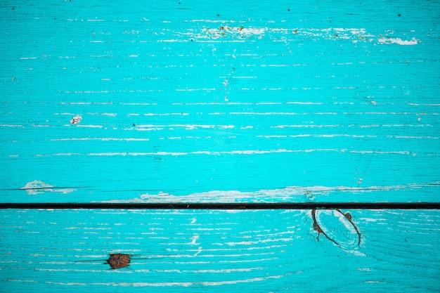 Старая деревянная покрашенная деревенская стена с голубой облупленной краской. увядшая деревянная планка крупным планом. пилинг краски на борту. поврежденная грубая деревянная текстура с винтом. несовершенная текстура поверхности дерева. фон с выветрившейся краской.