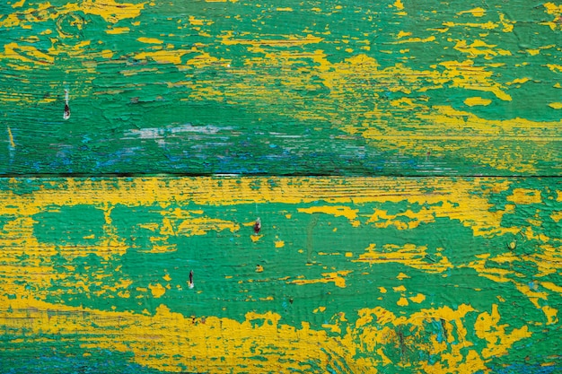 Старая деревянная покрашенная деревенская стена с облупленной краской желтого зеленого цвета. увядшая деревянная планка крупным планом. пилинг краски на борту. поврежденная грубая деревянная текстура. несовершенная поверхность древесины. фон с выветрившейся краской.