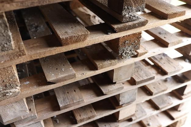 Старые деревянные поддоны, сложенные друг на друга крупным планом, мебель из концепции поддонов