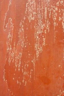 Старые деревянные панели с облупившейся красной поверхностью с царапинами. вертикальное изображение.
