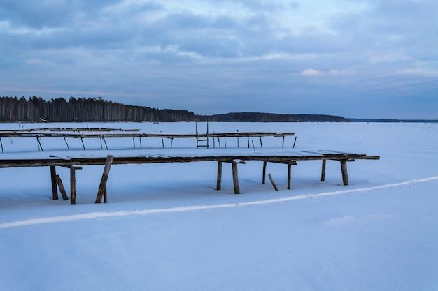 눈 속에서 오래 된 목재 부두입니다. 얼어 붙은 호수와 소나무 숲