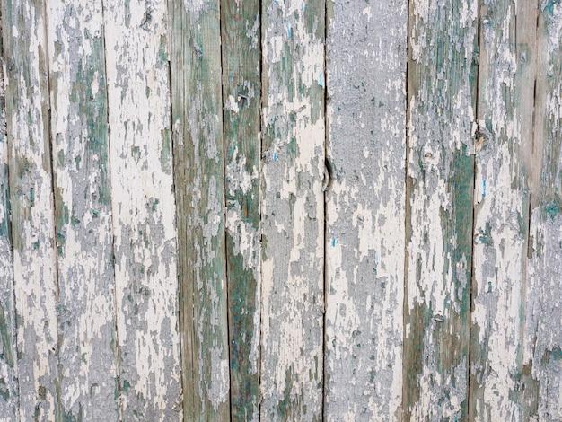 白と緑のペンキをはがして塗られた古い木の板。