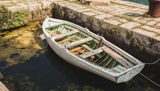 고대 석조 부두에 계류하는 오래 된 목조 노 젓는 배