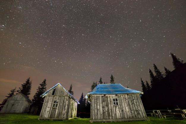 Old wooden shepherd huts on mountains clearing under starry sky.