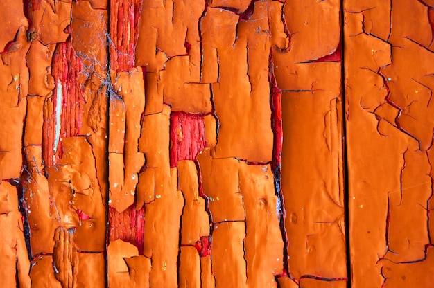 Старый деревянный щит окрашен в оранжевый с царапинами и сколы.