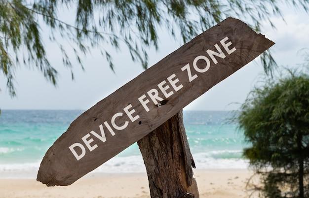 熱帯のビーチでテキストデバイスフリーゾーンと古い木製看板