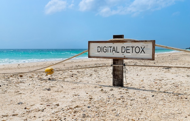 Old wooden sign with text digital detox on tropical beach