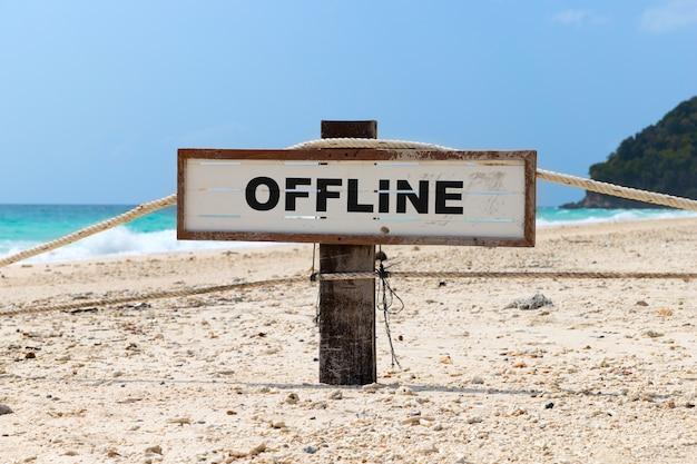 熱帯のビーチでオフラインのテキストで古い木製看板