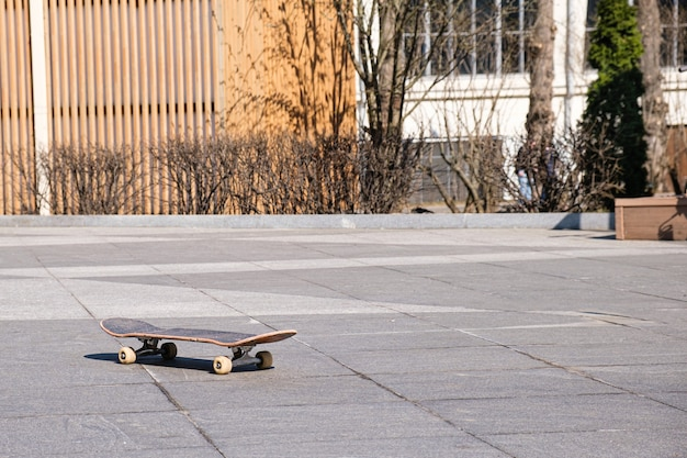 Old wooden skateboard on skating rink in an openair park.