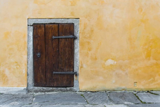 Old wooden small door on the yellow rustic wall