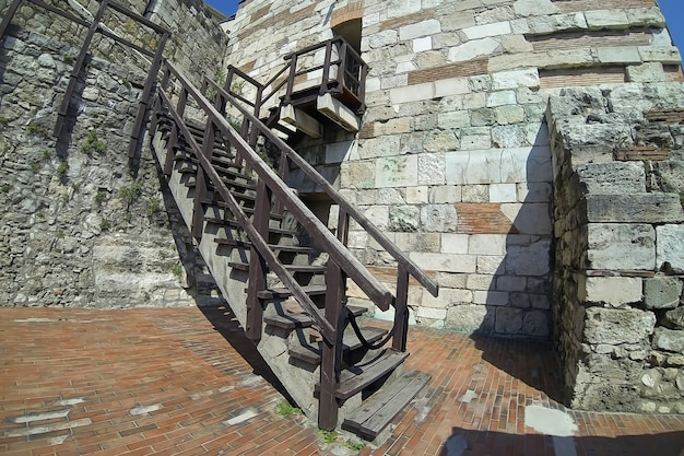 Old wooden staircase outside a stone castle