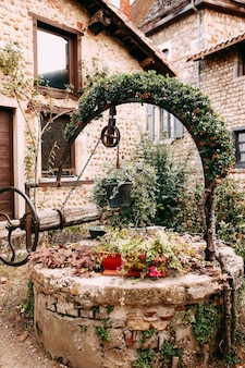 Old wooden stone well with red flower arch and ivy in perouges, france. high quality photo
