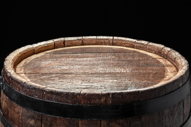Old wooden surface barrel on a dark