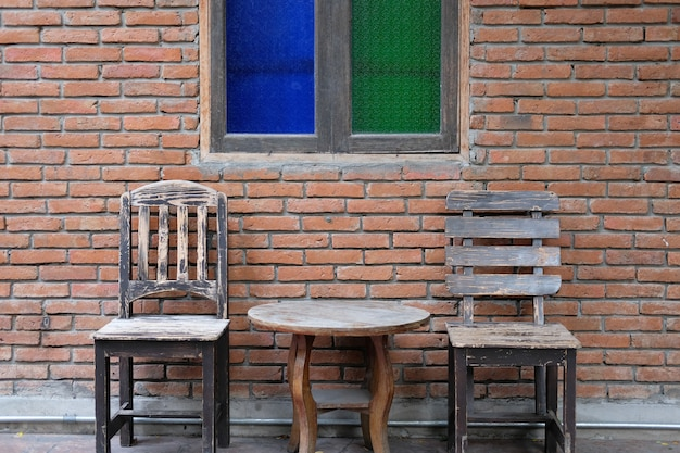 Old wooden table & chair near brick wall