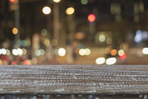 Old wooden table on front and blurred colorful street