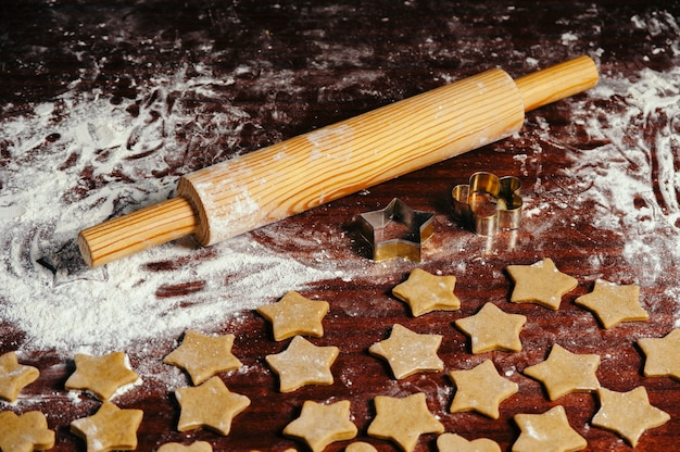 On the old wooden table lies a rolling pin with flour and raw dough in the form of asterisk. christmas cookies.