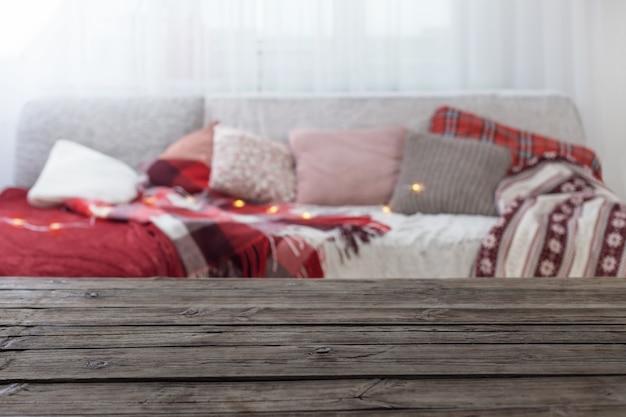 Старый деревянный стол на фоне дивана с подушками и пледами