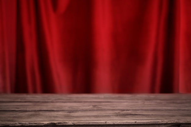 背景のベルベットのカーテンに古い木製のテーブル