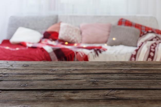 Старый деревянный стол на диване с подушками и пледами